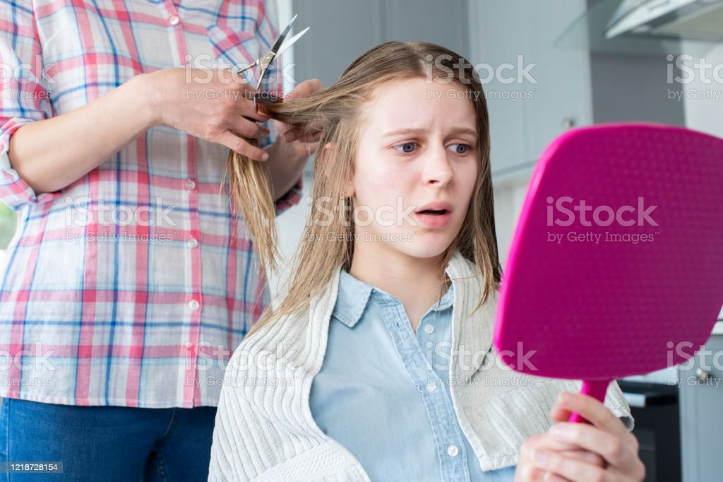 Mutter schneiden unglücklich Teenage Töchter Haare zu Hause während Lockdown - Lizenzfrei 14-15 Jahre Stock-Foto