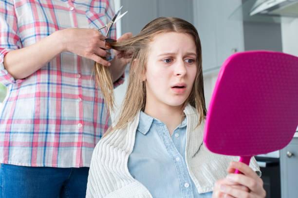 mutter schneiden unglücklich teenage töchter haare zu hause während lockdown - cut wrong hair stock-fotos und bilder
