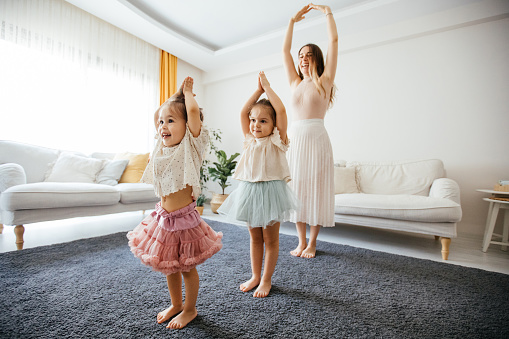 Mother dancing with preschool daughters at home