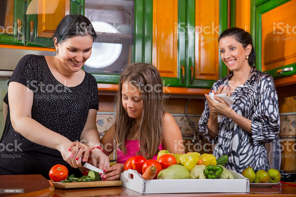 Mother, daughter and aunt have fun in the kitchen stock photo