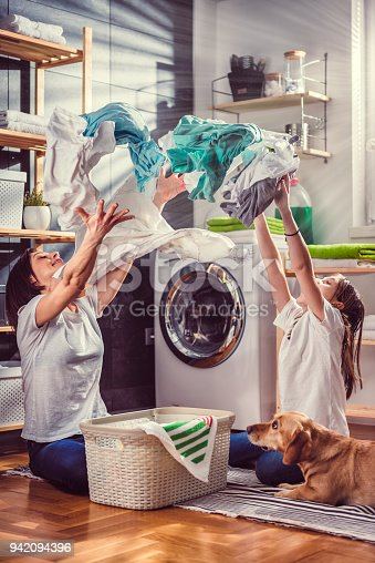 istock Mother, daughter and dog having fun at laundry room 942094396