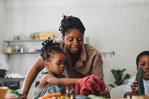 Beautiful mother is with her kids at the table, smiling and overlooking them playing with vegetables preparing them for lunch.