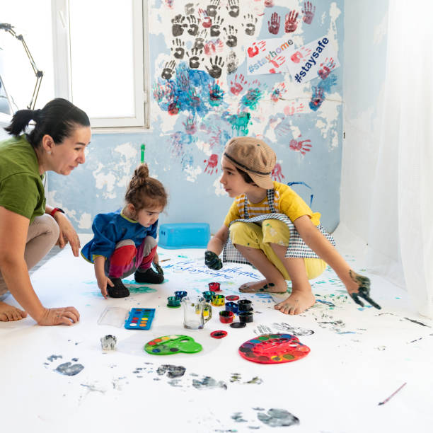 Mother, Daughter And Son Finger Painting At Home stock photo