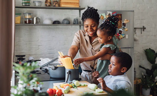 Happy African American mother, daughter and son preparing spaghetti and vegetables for lunch over a kitchen sink.
