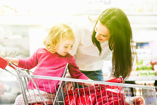 mutter und tochter kind, supermarkt, einkaufswagen, einkaufsmöglichkeiten, lächeln, alltag, - kinderhandtaschen stock-fotos und bilder