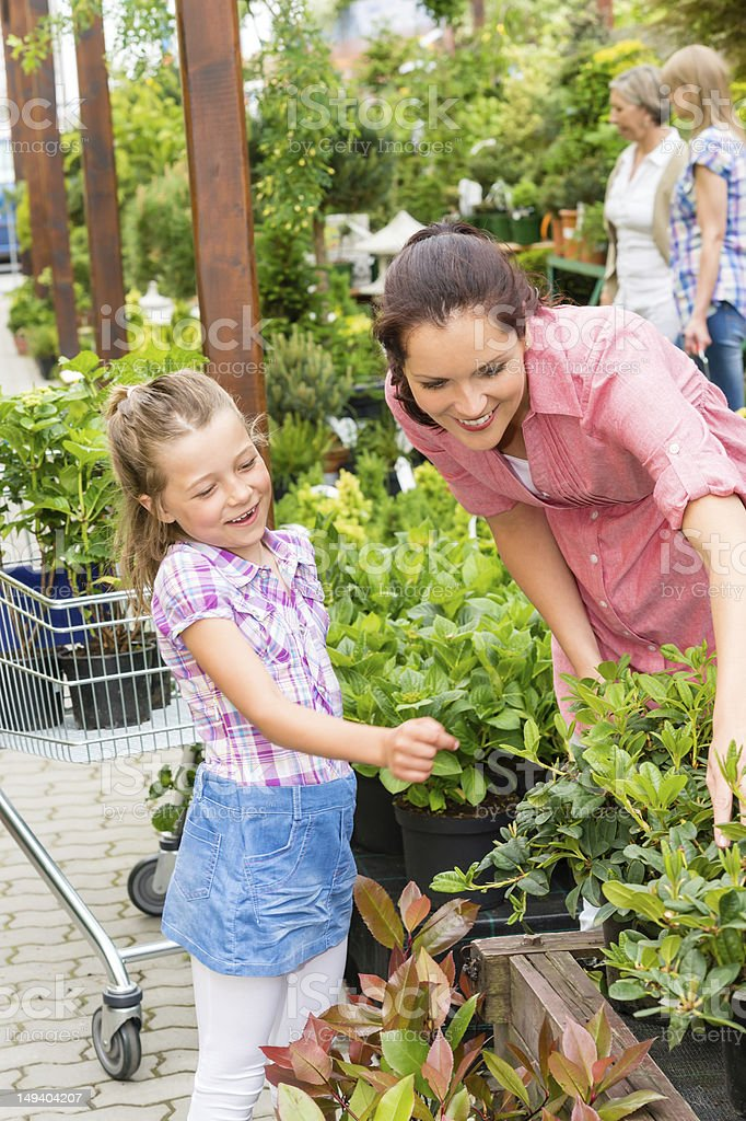 Mother daughter choosing flowers in garden shop royalty-free stock photo