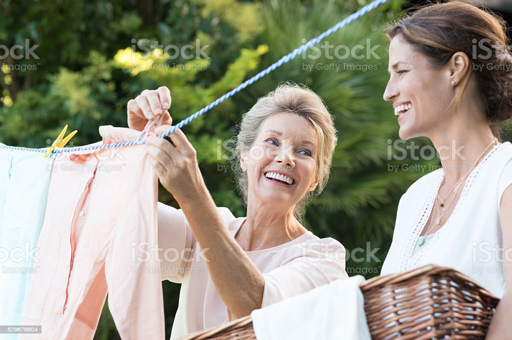 Mother daughter doing laundry stock photo