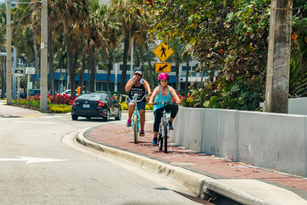 Mother daughter riding bicycles on the sidewalk stock photo
