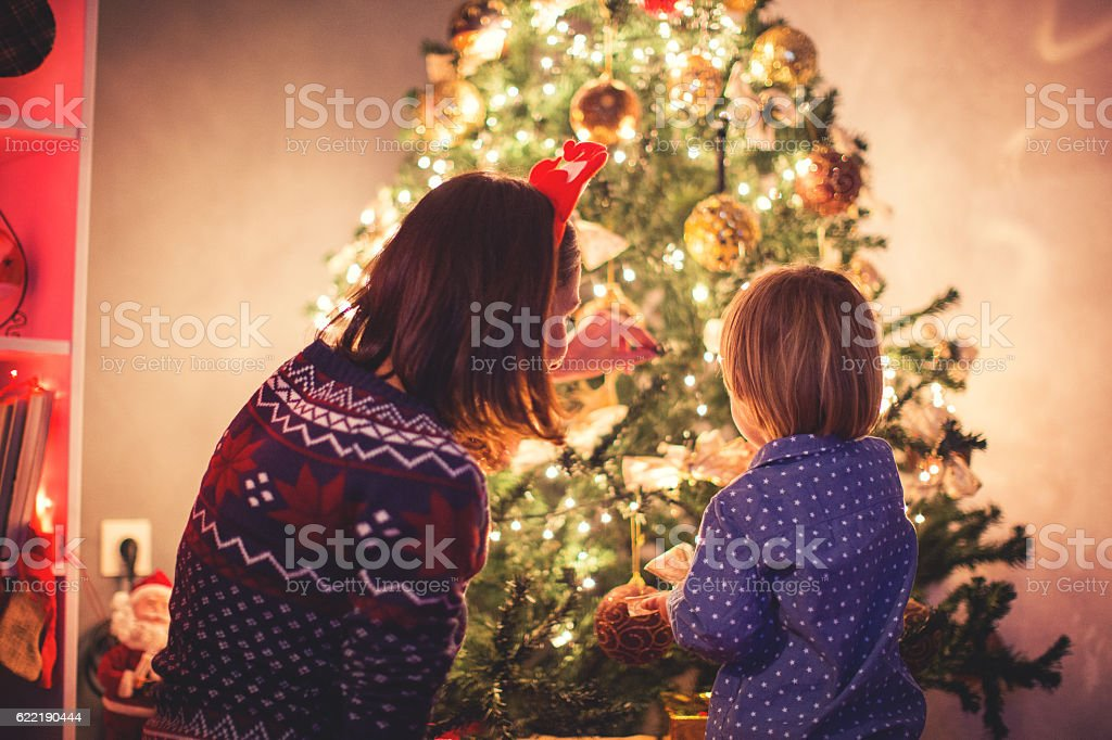 Mother decorating Christmas tree with her son stock photo