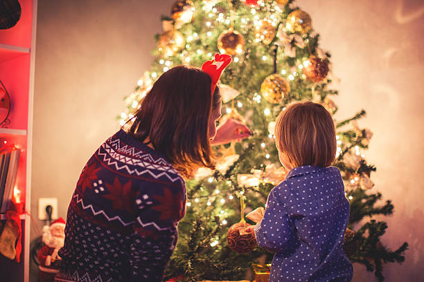 mother decorating christmas tree with her son - decorating stock photos and pictures