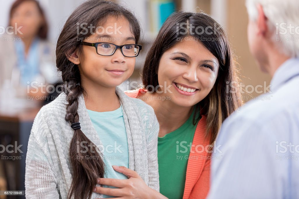 Mother discusses daughter's symptoms with male pediatrician stock photo
