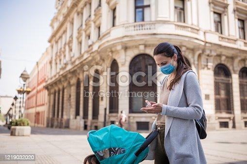 Mother disinfect her hands on the street. Belgrade, Serbia