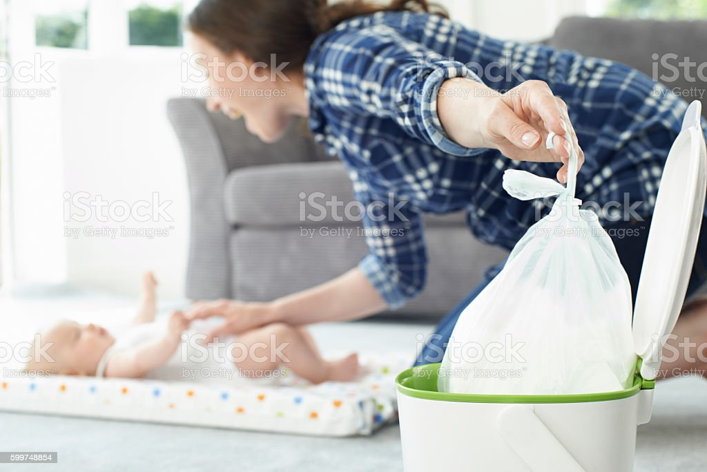 Mother Disposing Of Baby Nappy In Bin stock photo