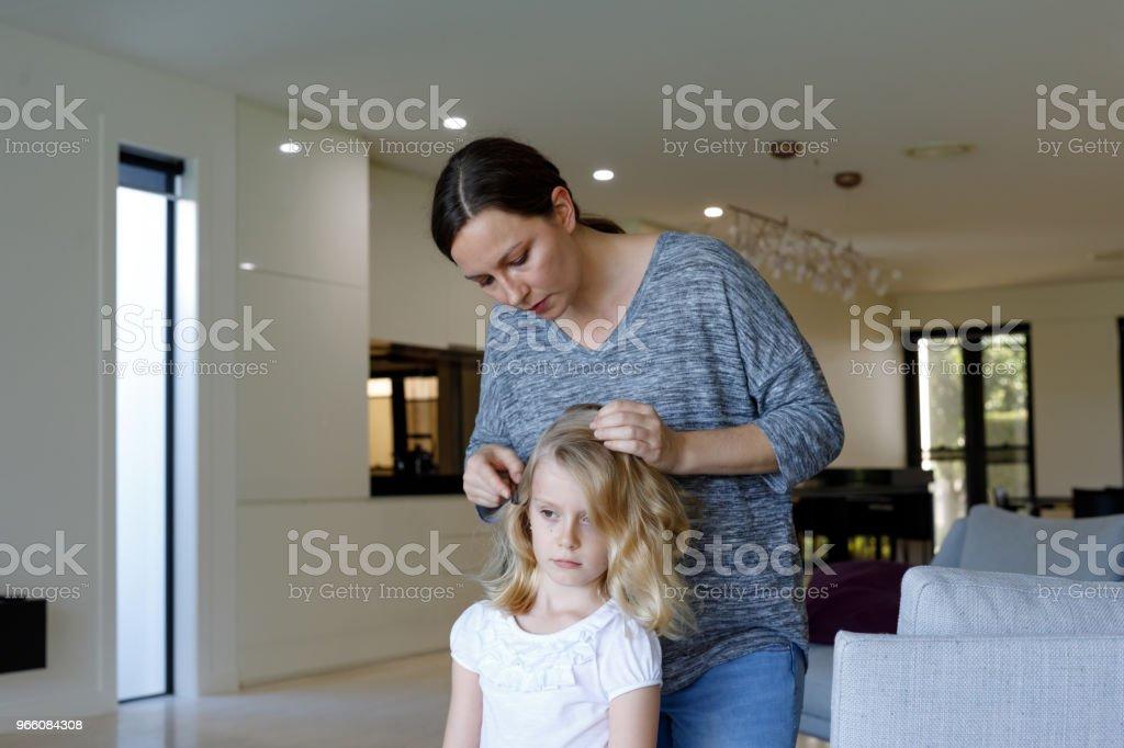 Mor gör huvudet löss inspektion på dotter - Royaltyfri 6-7 år Bildbanksbilder