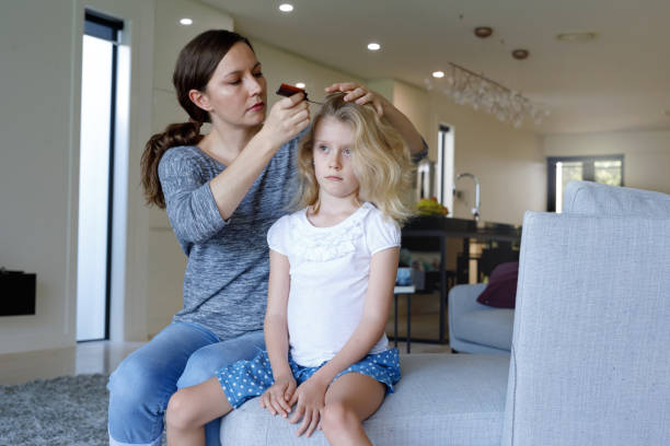 Mother Doing Head Lice Inspection On Daughter stock photo