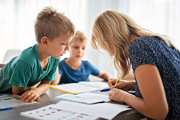 Mother doing homework with her sons. stock photo
