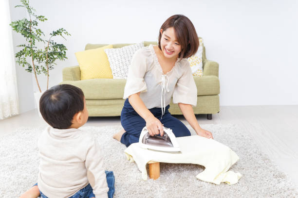 Mother doing household chores and child stock photo
