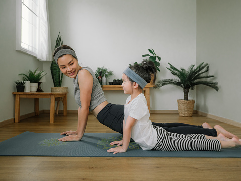 Mother doing on yoga mat with little daughter at home.