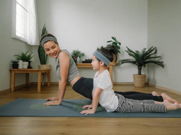 mãe fazendo em tapete de ioga com a filhinha em casa. - meditation - fotografias e filmes do acervo
