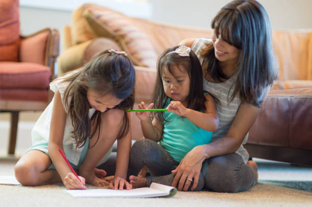 mother drawing with daughters in living room - hawaiian ethnicity stock photos and pictures