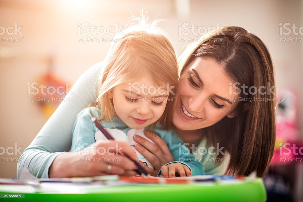 Mother drawing with her daughter stock photo