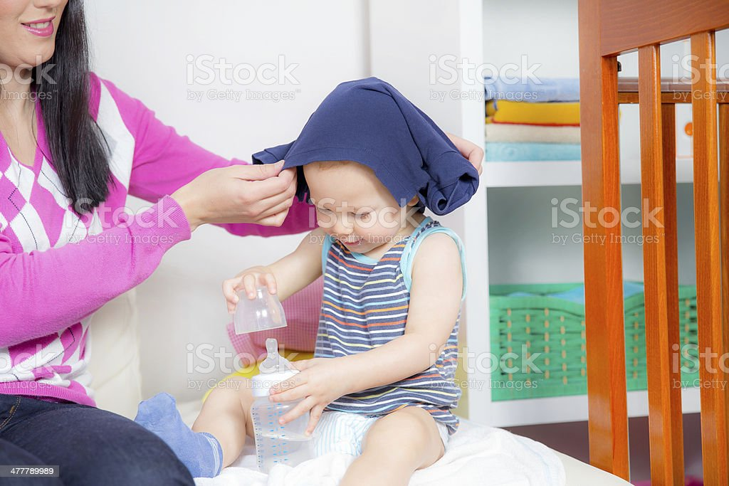 mother dresses her baby boy royalty-free stock photo