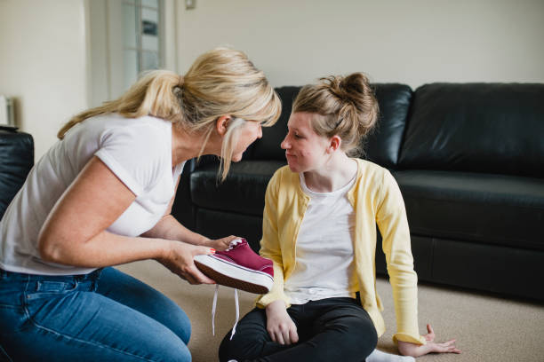 Mother Dressing Disabled Daughter at Home Mother is putting her disabled daughter's shoes on at home. als stock pictures, royalty-free photos & images