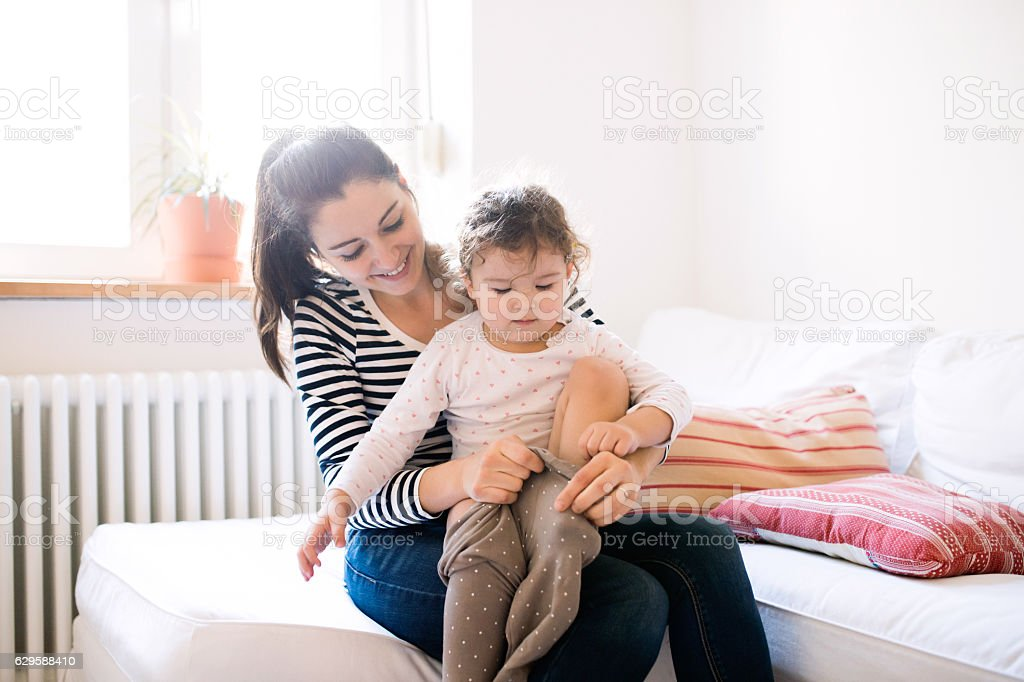Mother dressing her daughter in the morning on a couch stock photo