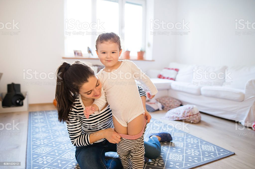 Mother dressing her daughter in the morning their living room stock photo