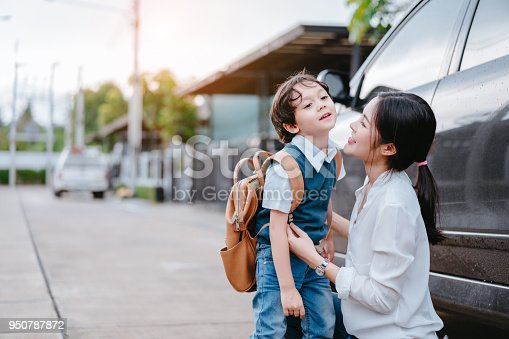 istock Mother dressing up a son and sending to school, Parent and pupil going to kindergarten of preschool first day. 950787872