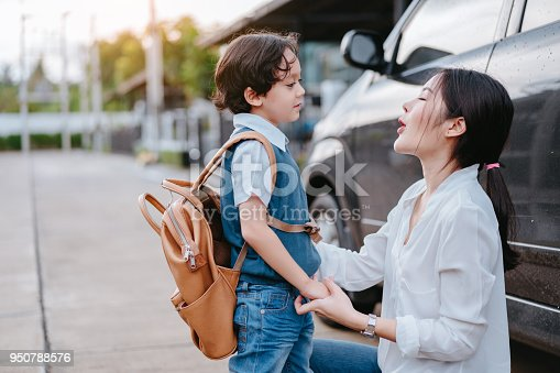 istock Mother dressing up a son and sending to school, Parent and pupil going to kindergarten of preschool first day back to school concept. 950788576