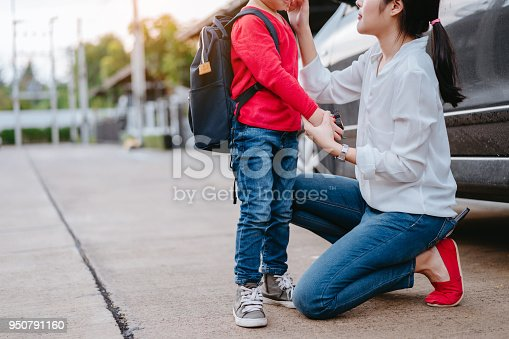 istock Mother dressing up a son and sending to school, Parent and pupil going to kindergarten of preschool first day back to school concept. 950791160