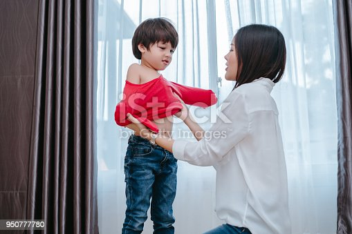 istock Mother dressing up a son for beginner school lessen and first day at room to going kindergarten education, parent protection boy concept. 950777780