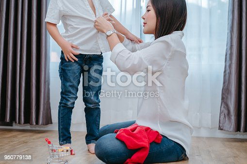 istock Mother dressing up a son for beginner school lessen and first day at room to going kindergarten education, parent protection boy concept. 950779138