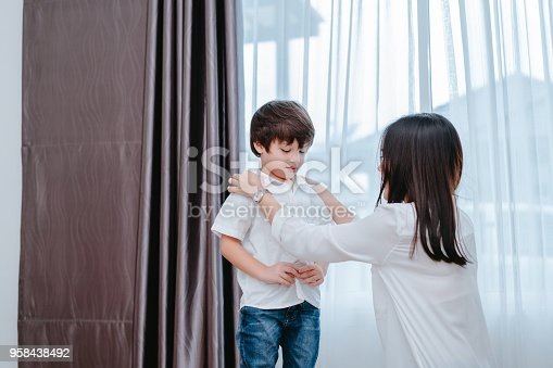 istock Mother dressing up a son for beginner school lessen and first day at room to going kindergarten education, parent protection boy concept. 958438492