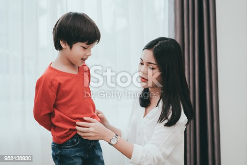 istock Mother dressing up a son for beginner school lessen and first day at room to going kindergarten education, parent protection boy concept. 958438930