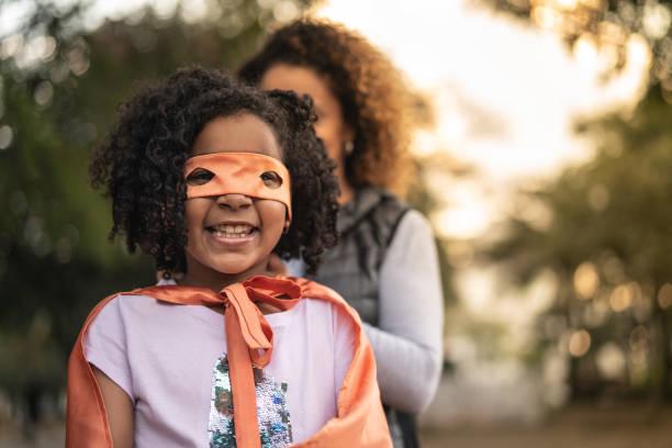 mamma klär hennes dotter kostym av super hero - superwoman barn bildbanksfoton och bilder