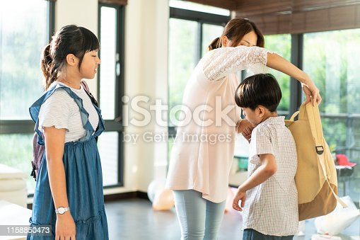 istock Mother dressing up son for school in the morning 1158850473