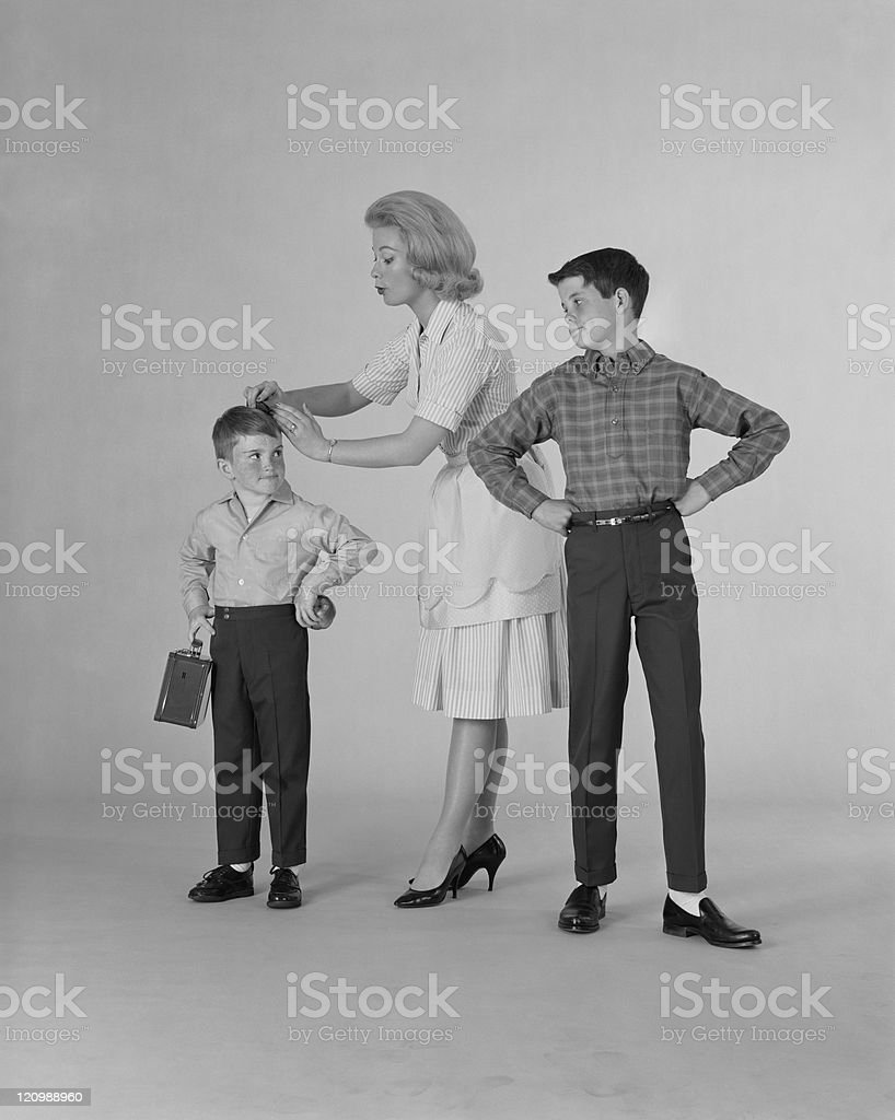 Mother dressing up two sons on white background royalty-free stock photo