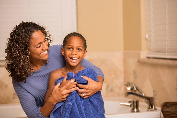 mutter trocknen an sohn nach seinem bad.  home badezimmer. - kinderbadewanne stock-fotos und bilder