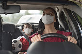 Latin American Mother driving her son to soccer practice wearing a facemask to avoid an infectious disease – COVID-19 lifestyle concepts