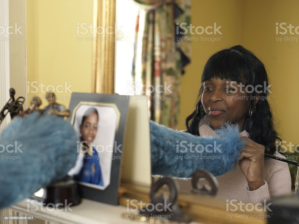 Mother dusting sons photograph above fireplace, smiling royalty-free stock photo