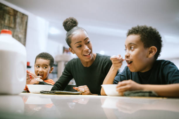 Mother Eating Breakfast With Her Two Boys stock photo