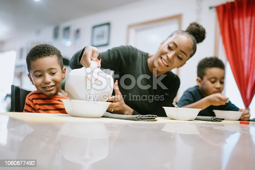 A mom sits at a table eating cereal with her sons at home. She pours milk into his bowl.