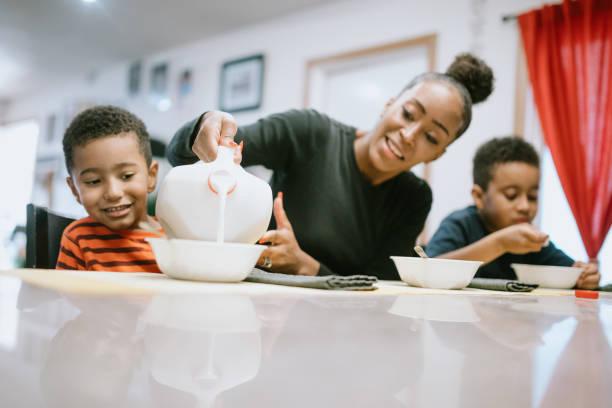 moeder eten ontbijt met haar twee jongens - alleenstaande moeder stockfoto's en -beelden