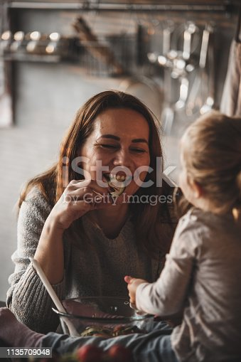istock Mother eating slice of cucumber in front of her baby daughter 1135709048