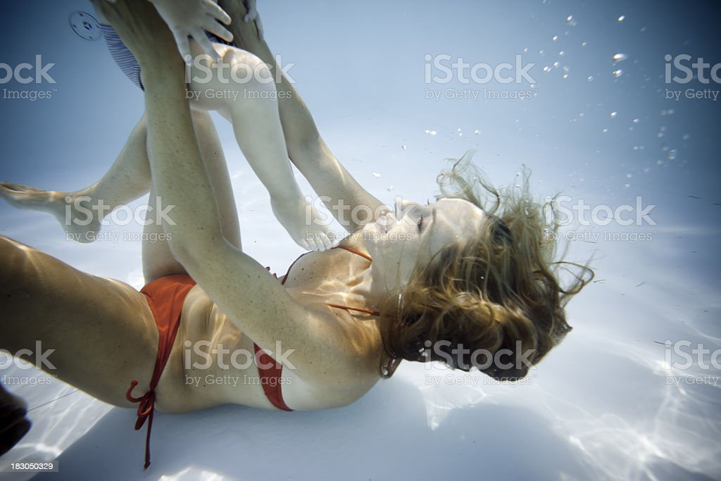 Mother embraces her child underwater royalty-free stock photo