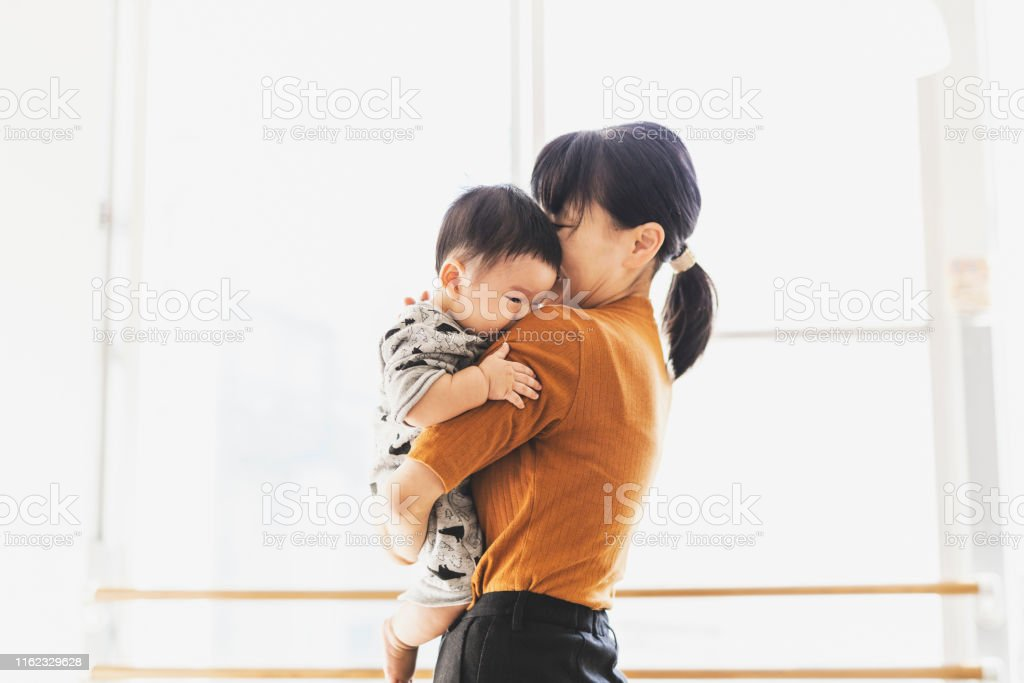 Mother embracing her baby Asian mother and son relaxed at cafe. Affectionate Stock Photo