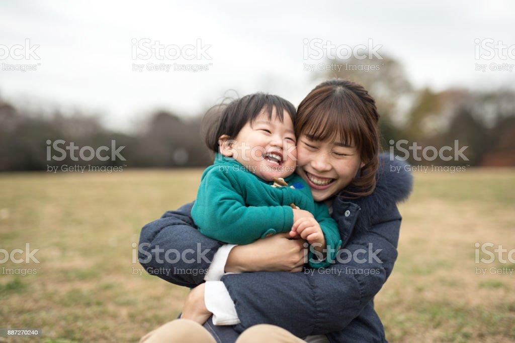 草の上の彼女の子を抱く母親 ストックフォト