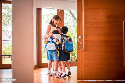 670900812istockphoto Mother embracing her children when coming home 968062660